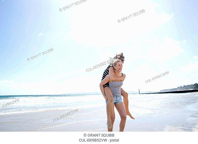 Sisters playing piggyback on beach