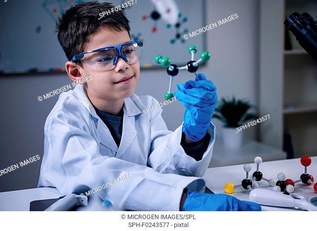 Schoolboy holding molecular model