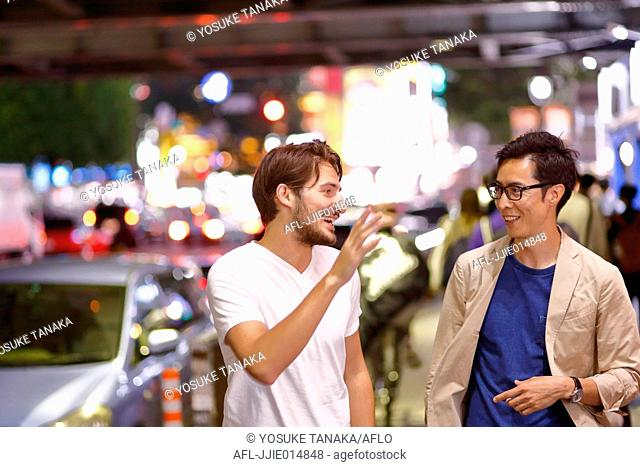 Caucasian man enjoying nightlife in Tokyo with Japanese friend, Japan