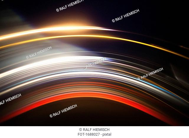 Various abstract light trails against black background