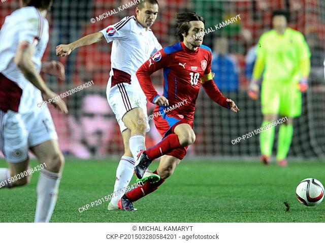 Tomas Rosicky of Czech Republic, right, and Arturs Zjuzins of Latvia, fight for a ball during the Euro 2016 group A qualifying soccer match between Czech...
