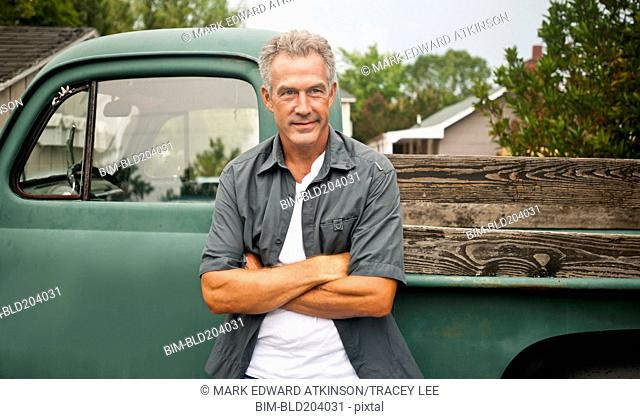Caucasian farmer leaning against truck outdoors