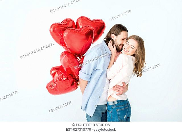 Young couple holding heart shaped air balloons and embracing on white