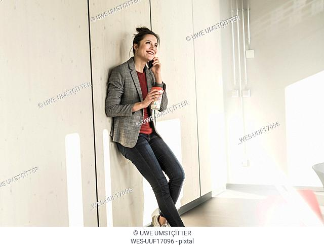 Smiling businesswoman leaning against a wall in office talking on cell phone