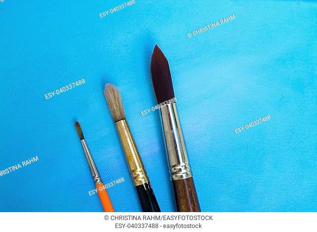 Brushes on blue painted canvas background texture background, concept for grades in school development, creative expression artist concept