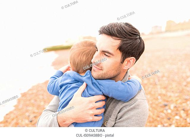 Father hugging young son on pebble beach