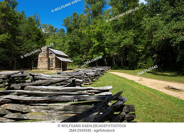 View of the John Oliver cabin from the 1820s in Cades Cove, Great Smoky Mountains National Park in Tennessee, USA, with a split rail fence in the foreground