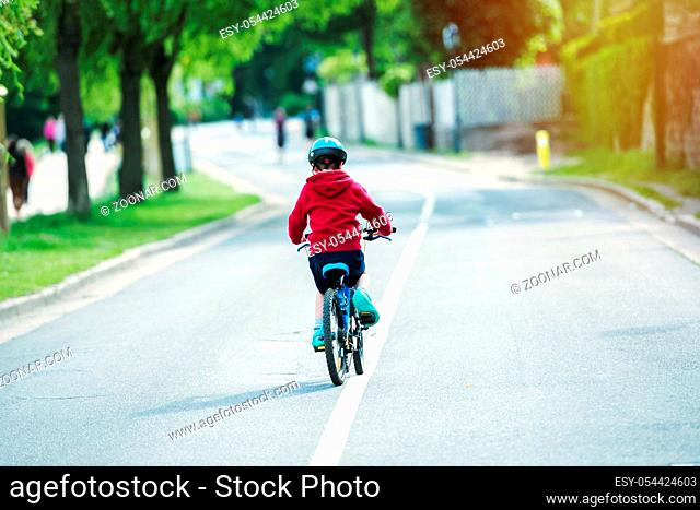 kid bicycling alone in the middle of the road