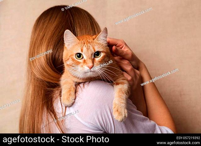 Happy ginger tabby cat on the woman's shoulder. Beautiful striped red cat on the shoulder blonde, beige background