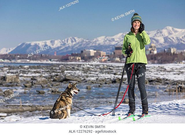 A young woman stops and talks on a cell phone while she skijors with her Alaska Husky sled dog down the Tony Knowles Coastal Trail, Anchorage