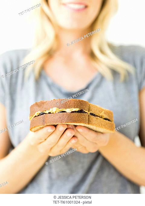 Woman holding sandwich with peanut butter