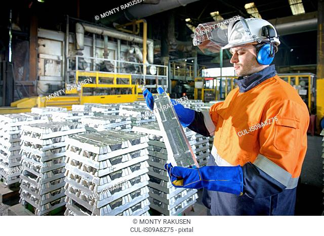 Warehouse worker checking aluminum ingot