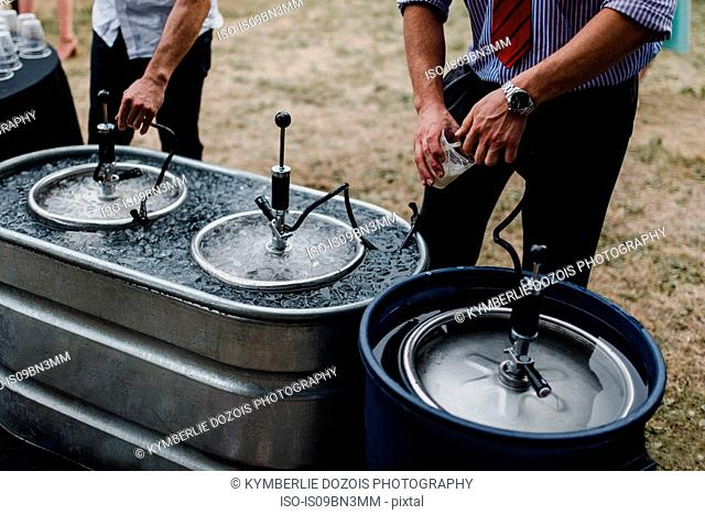 Men pouring beer from keg in cooling bath at barbecue, cropped
