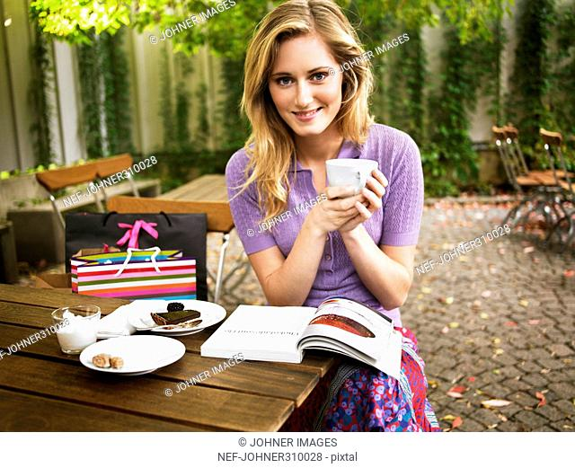 A young woman drinking coffee in a cafe outside