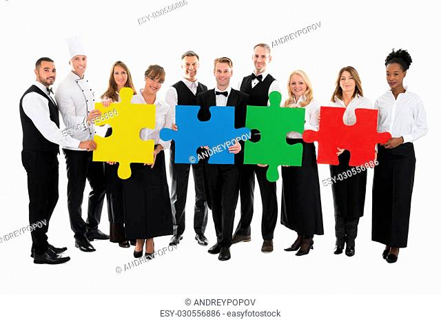 Portrait of confident restaurant staff joining jigsaw pieces against white background