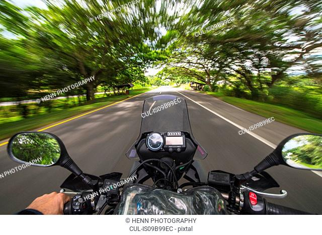 View from behind the handle bar of a driving motorbike, Pereira, Cordoba, Colombia