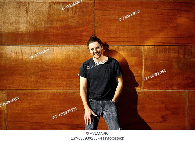 Hipster urban man portrait standing on city wall keeps the hand on his grey jeans smiling and looking at camera. Young adult enjoying sunny holidays under the...