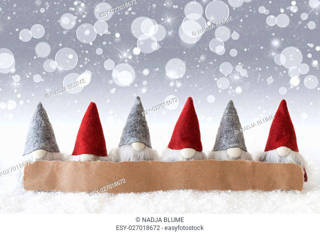 Label With Copy Space For Advertisement. Christmas Greeting Card With Gnomes. Sparkling Bokeh And Silver Background With Snow, Snowflakes And Stars