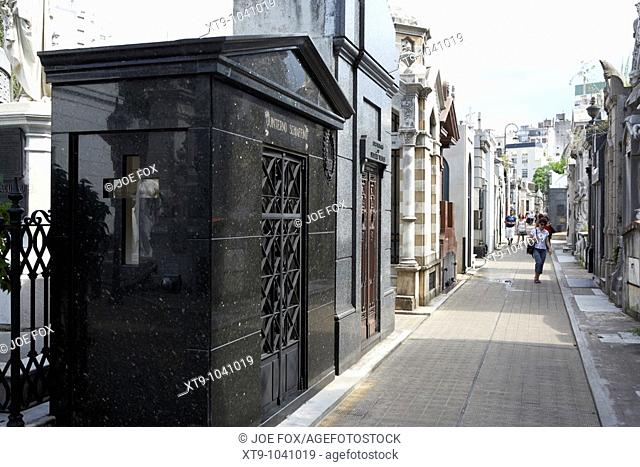 tourists walk row of older mausoleums on a street in recoleta cemetery capital federal buenos aires republic of argentina south america