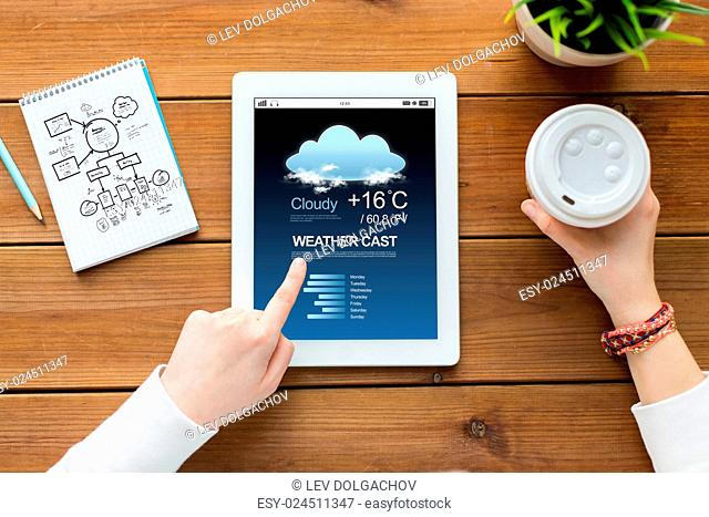 business, education, technology and people concept - close up of woman with weather forecast application on tablet pc computer screen