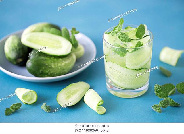 Water with cucumber strips, mint and ice on a blue surface