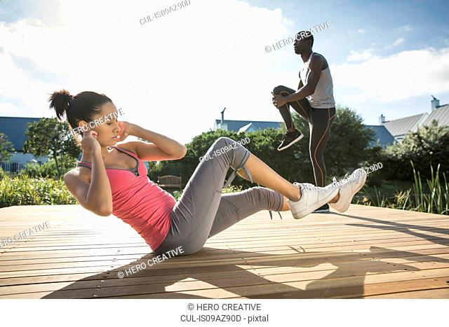 Side view of couple on wooden decking exercising