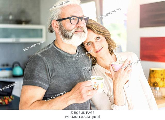 Mature couple drinking coffee in kitchen at home