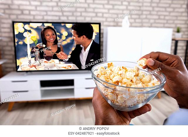 Close-up Of A Man Eating Popcorn While Watching Romantic Movie On Television