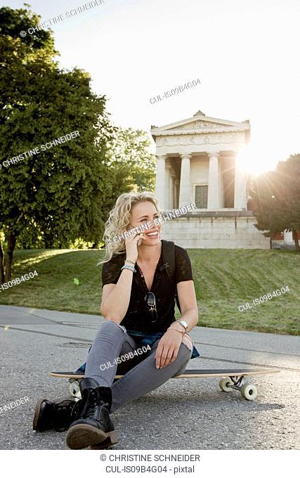 Female skateboarder sitting on skateboard in park making smartphone call
