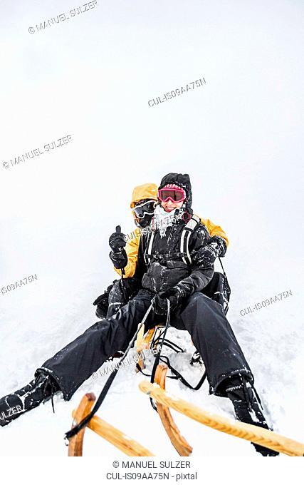 Young couple sitting on sledge, Bramberg am Wildkogel, Austria