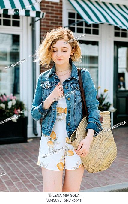 Young woman on street carrying straw bag, Menemsha, Martha's Vineyard, Massachusetts, USA