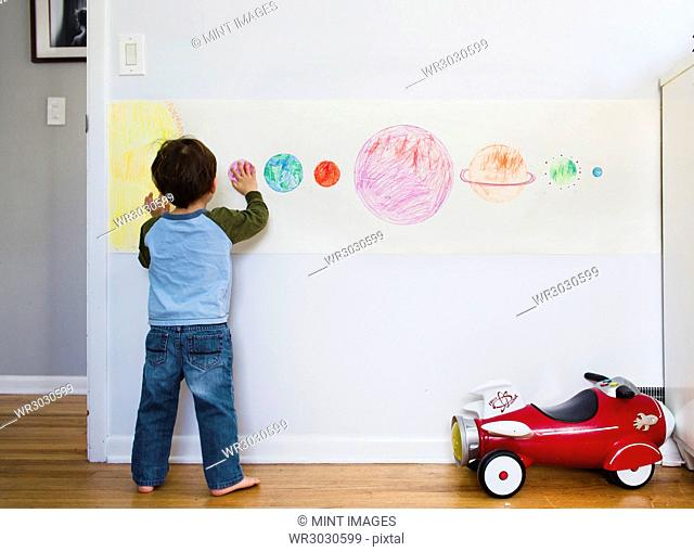 A child, boy looking at a drawing of the solar system planets on a wall