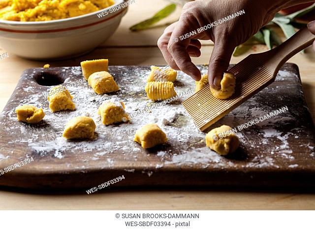 Preparing pumpkin gnocchi, rolling on wooden board