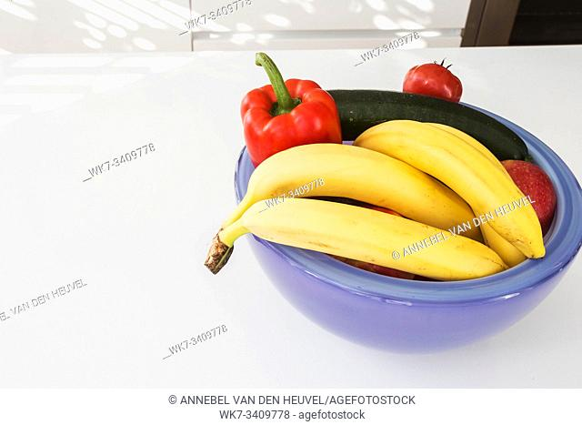Vegetables and fruit in a purple bowl on a white table closeup