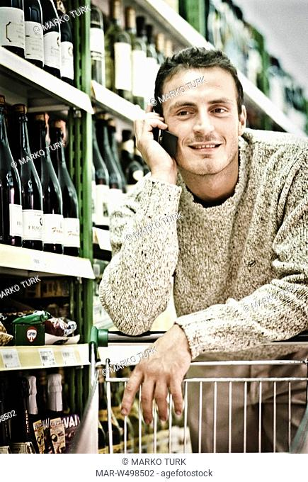 Man on a mobile phone in a supermarket