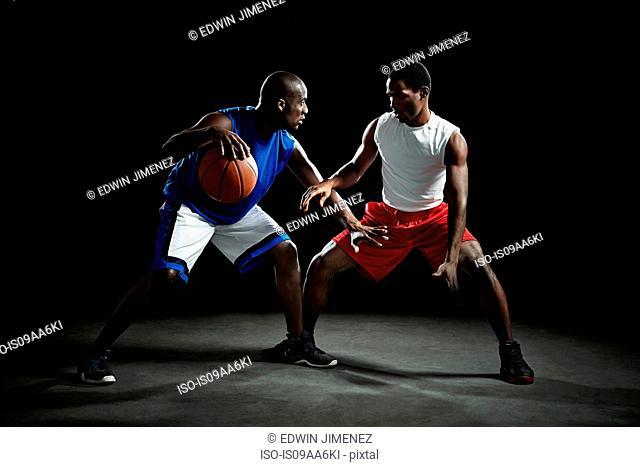 Basketball players competing for ball