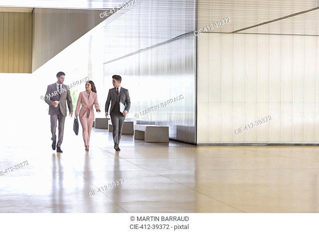 Business people walking an talking in modern office corridor