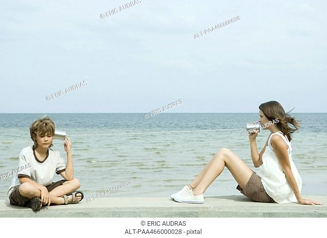Boy and teen sister sitting next to water, talking to each other through tin can phone