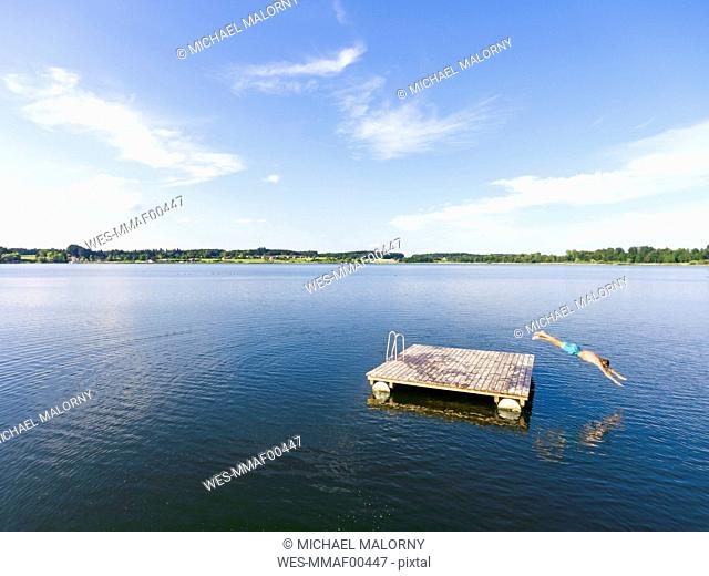 Man jumping from bathing platform into water