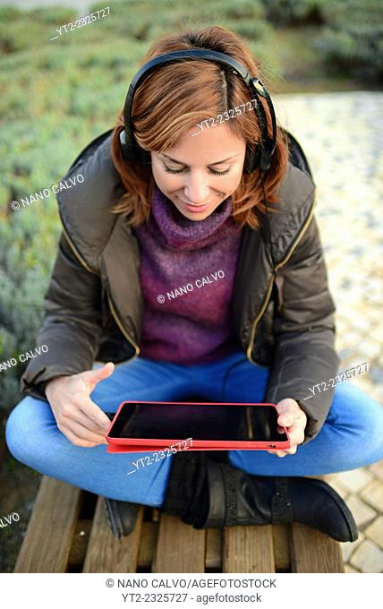 Exterior portrait of young woman using tablet with headphones