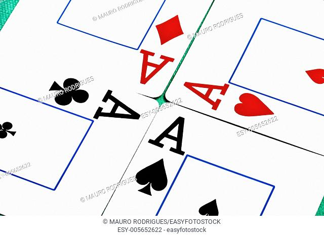 Close up view of a set of four aces spread on a green cloth table