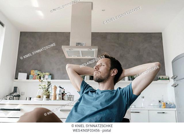 Pensive man with hands behind head sitting in the kitchen looking at distance