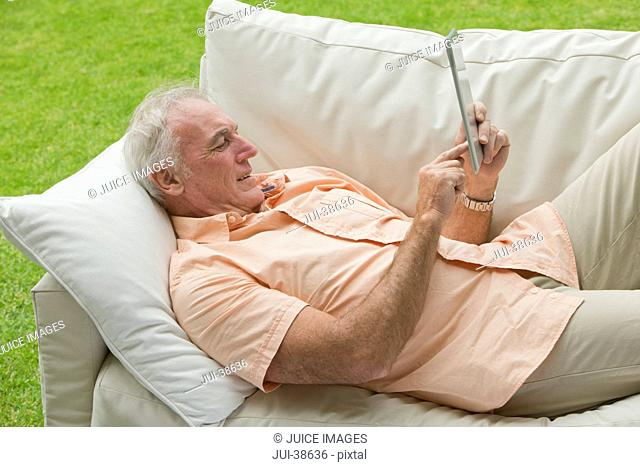 Senior man laying on outdoor sofa and using digital tablet