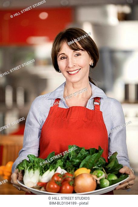 Caucasian woman holding platter of vegetables