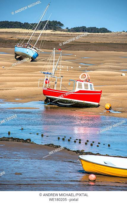 Colourful boats marooned on sandbanks at low tide on East Fleet river estuary at Wells next the sea, North Norfolk coast, East Anglia, England, UK