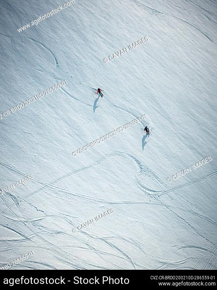 Two men skiing on snow in Iceland from overhead angle