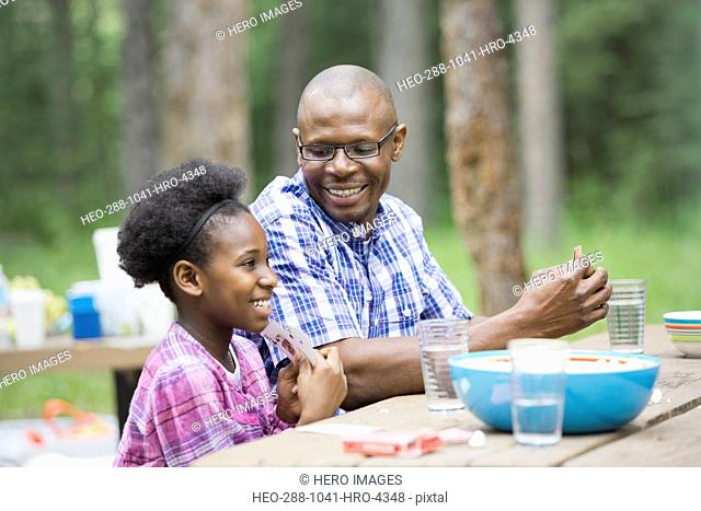 Happy father and daughter playing cards at picnic table