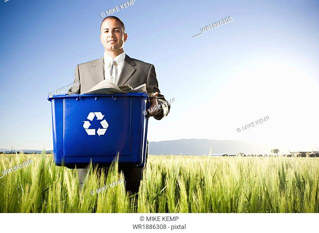 businessman holding a recycling bin