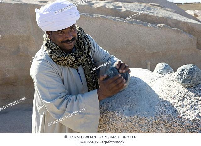 Guard demonstrating the processing of the stones, unfinished obelisk, stone quarry, Assuan, Egypt, Africa