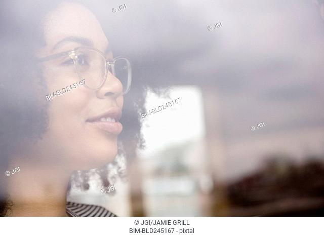 Smiling African American woman behind window